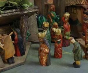 Små treskulpturer av de tre vise menn som nærmer seg stallen med Jesusbarnet, Josef og Maria